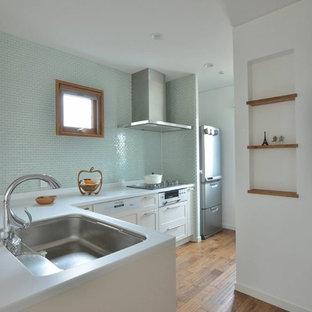 他の地域の北欧スタイルのおしゃれなキッチン (シングルシンク、落し込みパネル扉のキャビネット、白いキャビネット、青いキッチンパネル、無垢フローリング、茶色い床) の写真