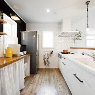 他の地域のアジアンスタイルのおしゃれなII型キッチン (一体型シンク、フラットパネル扉のキャビネット、白いキャビネット、無垢フローリング、茶色い床) の写真