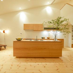 他の地域のアジアンスタイルのおしゃれなキッチン (シングルシンク、フラットパネル扉のキャビネット、中間色木目調キャビネット、木材カウンター、淡色無垢フローリング、茶色い床、茶色いキッチンカウンター) の写真