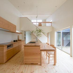 他の地域のアジアンスタイルのおしゃれなキッチン (シングルシンク、フラットパネル扉のキャビネット、中間色木目調キャビネット、木材カウンター、茶色いキッチンパネル、木材のキッチンパネル、淡色無垢フローリング、ベージュの床、茶色いキッチンカウンター) の写真