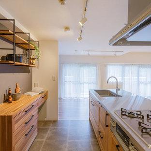 他の地域の北欧スタイルのおしゃれなキッチン (シングルシンク、フラットパネル扉のキャビネット、茶色いキャビネット、ステンレスカウンター、スレートの床、グレーの床、茶色いキッチンカウンター) の写真
