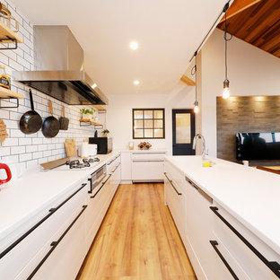 他の地域のインダストリアルスタイルのおしゃれなキッチン (一体型シンク、フラットパネル扉のキャビネット、白いキャビネット、白いキッチンパネル、無垢フローリング、茶色い床、白いキッチンカウンター) の写真