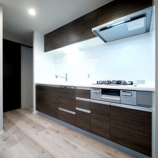This is an example of a modern single-wall open plan kitchen in Tokyo with dark wood cabinets, white splashback, plywood flooring, an island and beige floors.