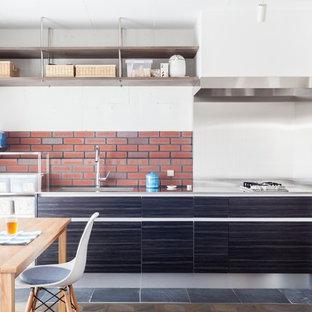 東京23区の中サイズのアジアンスタイルのおしゃれなキッチン (一体型シンク、フラットパネル扉のキャビネット、黒いキャビネット、ステンレスカウンター、メタルタイルのキッチンパネル、黒い調理設備、スレートの床、アイランドなし) の写真