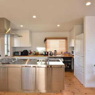 他の地域のモダンスタイルのおしゃれなキッチン (一体型シンク、フラットパネル扉のキャビネット、ステンレスキャビネット、ステンレスカウンター、淡色無垢フローリング、茶色い床、茶色いキッチンカウンター) の写真