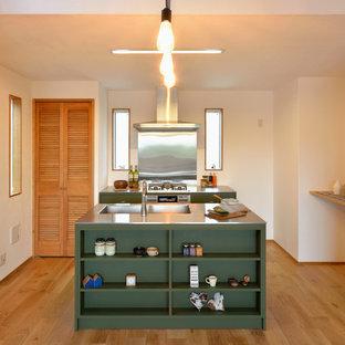 横浜のアジアンスタイルのおしゃれなアイランドキッチン (シングルシンク、フラットパネル扉のキャビネット、緑のキャビネット、ステンレスカウンター、淡色無垢フローリング) の写真