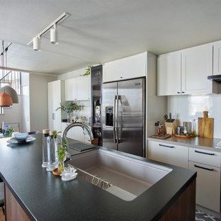 横浜の中くらいのコンテンポラリースタイルのおしゃれなキッチン (アンダーカウンターシンク、白いキャビネット、人工大理石カウンター、白いキッチンパネル、シルバーの調理設備、茶色い床、ベージュのキッチンカウンター、シェーカースタイル扉のキャビネット) の写真