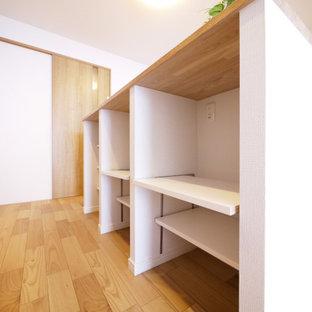 Skandinavisk inredning av ett flerfärgad linjärt flerfärgat kök med öppen planlösning, med skåp i mellenmörkt trä, vitt stänkskydd, plywoodgolv och beiget golv