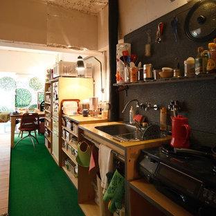 大阪のインダストリアルスタイルのおしゃれなキッチン (ドロップインシンク、オープンシェルフ、中間色木目調キャビネット、黒い調理設備、カーペット敷き) の写真