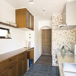 他の地域の地中海スタイルのおしゃれなキッチン (一体型シンク、落し込みパネル扉のキャビネット、濃色木目調キャビネット、ステンレスカウンター、茶色いキッチンパネル、モザイクタイルのキッチンパネル、テラコッタタイルの床、青い床、茶色いキッチンカウンター) の写真