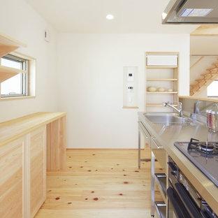 他の地域のおしゃれなキッチン (ステンレスカウンター、メタリックのキッチンパネル、白いキッチンカウンター) の写真
