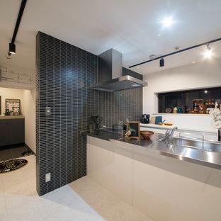 他の地域のインダストリアルスタイルのおしゃれなキッチン (アンダーカウンターシンク、白いキャビネット、ステンレスカウンター、黒いキッチンパネル、磁器タイルのキッチンパネル、白い床、白いキッチンカウンター) の写真