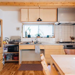 他の地域のラスティックスタイルのおしゃれなキッチン (一体型シンク、フラットパネル扉のキャビネット、中間色木目調キャビネット、ステンレスカウンター、白いキッチンパネル、磁器タイルのキッチンパネル、シルバーの調理設備の、無垢フローリング) の写真