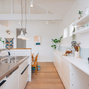 Scandinavian single-wall open plan kitchen in Other with an undermount sink, white cabinets, stainless steel benchtops, white splashback, porcelain splashback, plywood floors, with island and white benchtop.