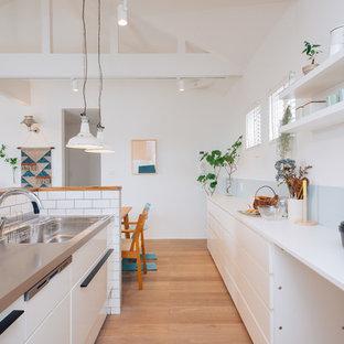 Aménagement d'une cuisine ouverte linéaire scandinave avec un évier encastré, des portes de placard blanches, un plan de travail en inox, une crédence blanche, une crédence en carreau de porcelaine, un sol en contreplaqué, un îlot central et un plan de travail blanc.