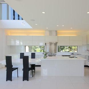 横浜の大きいモダンスタイルのおしゃれなキッチン (アンダーカウンターシンク、フラットパネル扉のキャビネット、白いキャビネット、人工大理石カウンター、白いキッチンパネル、セメントタイルのキッチンパネル、シルバーの調理設備の、セメントタイルの床、白い床) の写真
