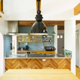 他の地域の北欧スタイルのおしゃれなキッチン (一体型シンク、ガラス扉のキャビネット、淡色木目調キャビネット、ステンレスカウンター、青いキッチンパネル、サブウェイタイルのキッチンパネル、淡色無垢フローリング) の写真