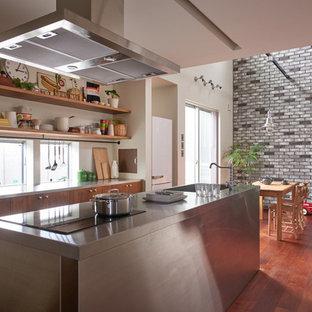 東京都下のインダストリアルスタイルのおしゃれなキッチン (一体型シンク、フラットパネル扉のキャビネット、濃色木目調キャビネット、ステンレスカウンター、白いキッチンパネル、シルバーの調理設備の、濃色無垢フローリング) の写真