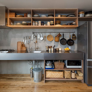 Industrial single-wall kitchen in Tokyo with an integrated sink, open cabinets, stainless steel benchtops, grey splashback, medium hardwood floors and brown floor.
