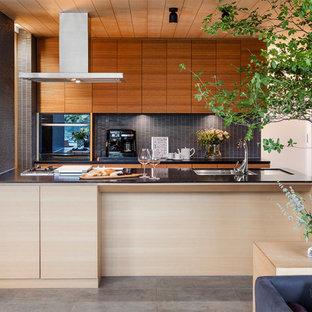 Modern inredning av ett linjärt kök med öppen planlösning, med en undermonterad diskho, släta luckor, skåp i ljust trä, grått stänkskydd, stänkskydd i stickkakel, svarta vitvaror och en halv köksö