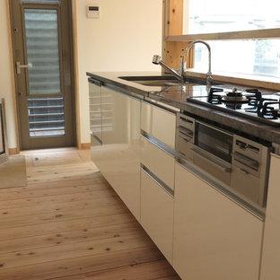 Diseño de cocina lineal, de estilo zen, de tamaño medio, abierta, con puertas de armario blancas, encimera de granito, salpicadero blanco, suelo de madera clara, suelo beige y encimeras turquesas