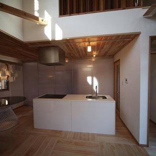 他の地域の小さいアジアンスタイルのおしゃれなキッチン (アンダーカウンターシンク、インセット扉のキャビネット、白いキャビネット、人工大理石カウンター、白いキッチンパネル、黒い調理設備、淡色無垢フローリング、ベージュの床、白いキッチンカウンター) の写真