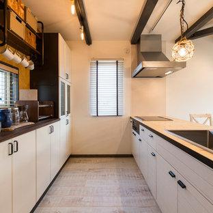 他の地域のインダストリアルスタイルのおしゃれなキッチン (シングルシンク、フラットパネル扉のキャビネット、白いキャビネット、木材カウンター、白い床) の写真