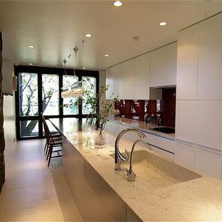 東京23区のモダンスタイルのおしゃれなペニンシュラキッチン (一体型シンク、フラットパネル扉のキャビネット、白いキャビネット、大理石カウンター、白い床) の写真