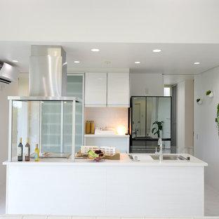 他の地域のモダンスタイルのおしゃれなキッチン (白いキャビネット、人工大理石カウンター、白い床、白いキッチンカウンター、シングルシンク、フラットパネル扉のキャビネット) の写真