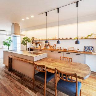 他の地域の北欧スタイルのおしゃれなアイランドキッチン (シングルシンク、フラットパネル扉のキャビネット、白いキャビネット、木材カウンター、淡色無垢フローリング) の写真