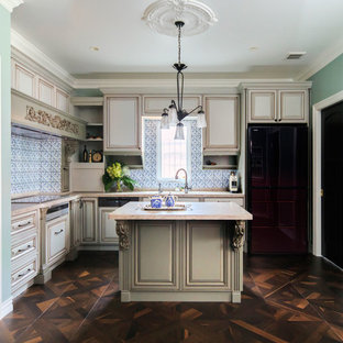 Large victorian eat-in kitchen ideas - Example of a large ornate l-shaped medium tone wood floor eat-in kitchen design in Tokyo with an undermount sink, raised-panel cabinets, beige cabinets, onyx countertops, blue backsplash, glass tile backsplash, black appliances and an island