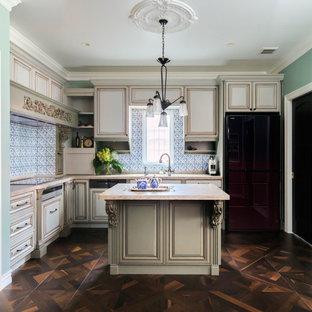 Inspiration pour une grande cuisine américaine victorienne en L avec un évier encastré, un placard avec porte à panneau surélevé, des portes de placard beiges, un plan de travail en onyx, une crédence bleue, une crédence en carreau de verre, un électroménager noir, un sol en bois brun et un îlot central.
