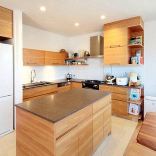 他の地域のコンテンポラリースタイルのおしゃれなキッチン (アンダーカウンターシンク、フラットパネル扉のキャビネット、中間色木目調キャビネット、白いキッチンパネル、黒い調理設備、ベージュの床、茶色いキッチンカウンター) の写真