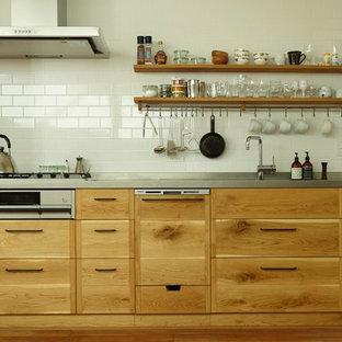 神戸のコンテンポラリースタイルのおしゃれなI型キッチン (一体型シンク、フラットパネル扉のキャビネット、ステンレスカウンター、茶色いキッチンパネル、セラミックタイルのキッチンパネル、無垢フローリング) の写真