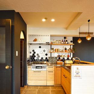 他の地域のコンテンポラリースタイルのおしゃれなL型キッチン (フラットパネル扉のキャビネット、淡色木目調キャビネット、ステンレスカウンター、マルチカラーのキッチンパネル、アイランドなし、グレーの床) の写真