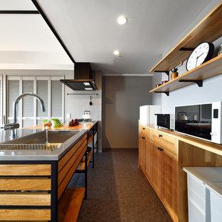 他の地域のインダストリアルスタイルのおしゃれなキッチン (シングルシンク、落し込みパネル扉のキャビネット、中間色木目調キャビネット、木材カウンター、グレーの床) の写真