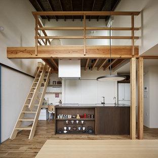 他の地域のアジアンスタイルのおしゃれなキッチン (アンダーカウンターシンク、フラットパネル扉のキャビネット、白いキャビネット、白いキッチンパネル、無垢フローリング、茶色い床、グレーのキッチンカウンター) の写真