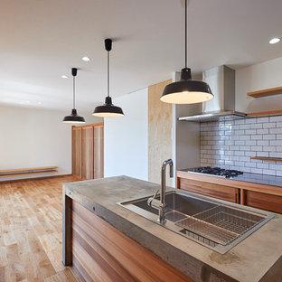 他の地域のアジアンスタイルのおしゃれなキッチン (ドロップインシンク、濃色木目調キャビネット、コンクリートカウンター、白いキッチンパネル、サブウェイタイルのキッチンパネル、シルバーの調理設備の、無垢フローリング、フラットパネル扉のキャビネット、ベージュの床) の写真
