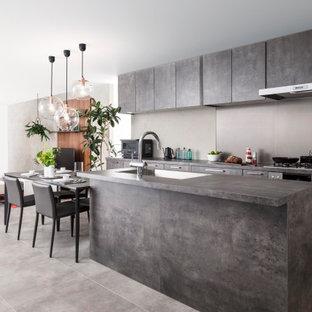 東京23区の広いコンテンポラリースタイルのおしゃれなキッチン (グレーのキャビネット、グレーのキッチンパネル、パネルと同色の調理設備、セラミックタイルの床、グレーの床、グレーのキッチンカウンター、ドロップインシンク、フラットパネル扉のキャビネット、磁器タイルのキッチンパネル) の写真