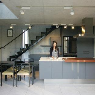 他の地域のコンテンポラリースタイルのおしゃれなキッチン (フラットパネル扉のキャビネット、グレーのキャビネット、シングルシンク、グレーのキッチンパネル、黒い調理設備、グレーのキッチンカウンター、グレーの床) の写真