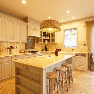 他の地域の広いシャビーシック調のおしゃれなキッチン (ドロップインシンク、レイズドパネル扉のキャビネット、白いキャビネット、淡色無垢フローリング、ベージュの床、白いキッチンカウンター) の写真