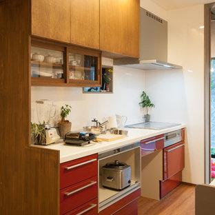Kleine, Einzeilige Asiatische Küche mit flächenbündigen Schrankfronten, roten Schränken, bunten Elektrogeräten und braunem Holzboden in Sonstige