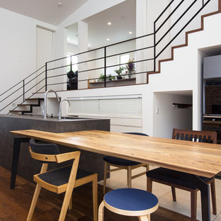 コンテンポラリースタイルのおしゃれなキッチン (アンダーカウンターシンク、フラットパネル扉のキャビネット、グレーのキャビネット、グレーのキッチンパネル、シルバーの調理設備の、無垢フローリング、茶色い床) の写真