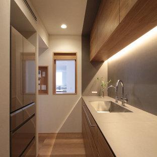 東京23区の中くらいのコンテンポラリースタイルのおしゃれなキッチン (アンダーカウンターシンク、フラットパネル扉のキャビネット、中間色木目調キャビネット、グレーのキッチンパネル、シルバーの調理設備、アイランドなし、ベージュの床、ベージュのキッチンカウンター) の写真