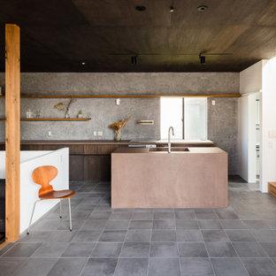 他の地域の広いコンテンポラリースタイルのおしゃれなキッチン (アンダーカウンターシンク、フラットパネル扉のキャビネット、中間色木目調キャビネット、グレーのキッチンパネル、パネルと同色の調理設備、グレーの床、茶色いキッチンカウンター) の写真