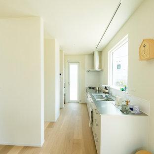 福岡の北欧スタイルのおしゃれなペニンシュラキッチン (一体型シンク、フラットパネル扉のキャビネット、白いキャビネット、ステンレスカウンター、淡色無垢フローリング、ベージュの床) の写真