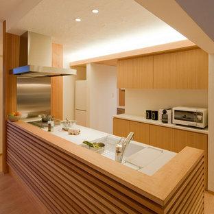 他の地域, の広い北欧スタイルのおしゃれなキッチン (一体型シンク、淡色木目調キャビネット、人工大理石カウンター、メタリックのキッチンパネル、白い調理設備、淡色無垢フローリング、アイランドなし、茶色い床) の写真