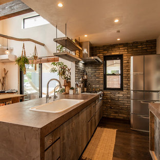 横浜のアジアンスタイルのおしゃれなキッチン (ドロップインシンク、フラットパネル扉のキャビネット、中間色木目調キャビネット、グレーのキッチンパネル、レンガのキッチンパネル、シルバーの調理設備の、濃色無垢フローリング、茶色い床、茶色いキッチンカウンター) の写真