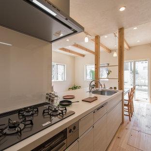 東京都下のカントリー風おしゃれなキッチン (シングルシンク、フラットパネル扉のキャビネット、淡色木目調キャビネット、淡色無垢フローリング、茶色い床) の写真