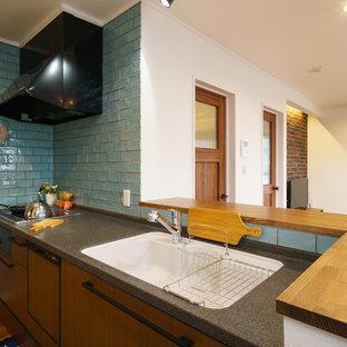 他の地域のビーチスタイルのおしゃれなキッチン (シングルシンク、フラットパネル扉のキャビネット、中間色木目調キャビネット、青いキッチンパネル、無垢フローリング、茶色い床) の写真